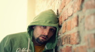Sad man standing by the brick wall portrait HD Stock Footage