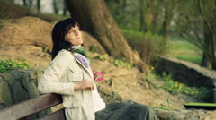 Young happy woman with flower relaxing on the park bench, dolly shot HD Stock Footage