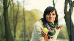 Young happy woman with flower and aplle in the park, dolly shot HD Stock Footage