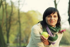 Young happy woman with flower and aplle in the park, dolly shot NTSC Stock Footage