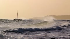 Sailboat and Surfers During Sunset Stock Footage