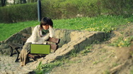 Attractive woman working on laptop in the park, dolly shot HD Stock Footage