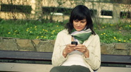 Attractive woman sending sms, texting in the park, dolly shot HD Stock Footage