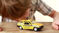 The boy playing with toy taxi car Stock Footage