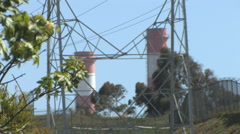 Rack Focus - Industrial Smoke Stacks With Electricity Tower - Tree in Foreground Stock Footage