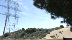 Wide Shot of Power Lines & Tower with Field & Sand Dune Below - stock footage