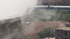 Train passes behind coal fired powerplant in Chinese city - stock footage