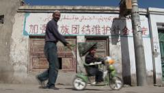 China, grandfather and child in front of Communist slogan, muslims, minority Stock Footage