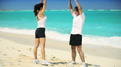 Young Couple in Sportswear Exercising on Beach - stock footage