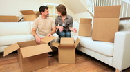 Stock Video Footage of Young Couple Unpacking House Moving Cartons