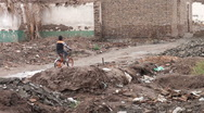Boy cycles through demolished Kashgar old town in Western China Stock Footage