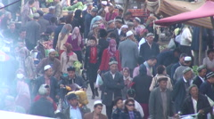 Muslim Uyghurs walk through busy bazaar in Kashgar in Western China Stock Footage