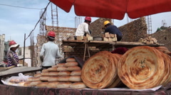 China, Kashgar, selling fresh bread in front of construction site Stock Footage