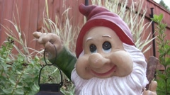 Sculpture of dwarf with lamp in hands in garden. Stock Footage