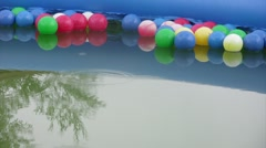 Rain drops fall in water of pool with balls. Stock Footage