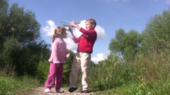 Little girl and boy stand in park, boy launch toy plane. - stock footage
