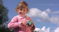 Little girl solves puzzle cube with earth pattern. - stock footage