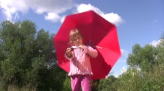 Little girl stands with an umbrella and twists it. Stock Footage