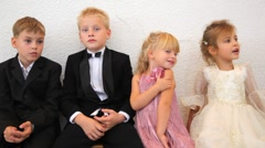Four children in celebratory clothes sit in room Stock Footage