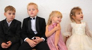 Stock Video Footage of Four children in celebratory clothes sit in room