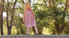 Smiling little girl goes on stone border Stock Footage