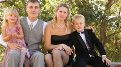Family in celebratory clothes sits on a bench. Stock Footage