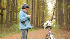 Boy with mobile phone stands near to bicycle in park. Stock Footage