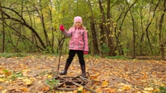 Girl searches for something in the hatch in park. Stock Footage