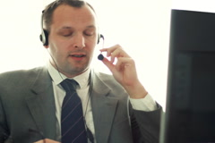 Male helpdesk consultant talking on headset NTSC - stock footage