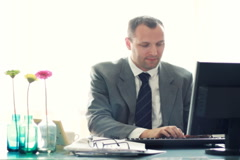 Businessman by the computer in the office showing ok sign NTSC Stock Footage