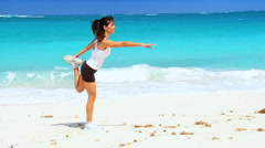 Young Female Doing Stretches on the Beach Stock Footage