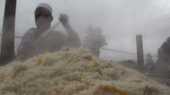Uyghur chef stirs a massive bowl of fresh pilaf rice at market in Western China Stock Footage
