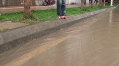 Child jumping over flooded Chinese street Stock Footage