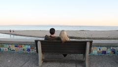 Young couple on boardwalk bench Stock Footage