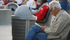Old man reading in city scene Stock Footage