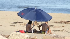 Beach umbrella couple Stock Footage