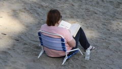 Heavyset woman reading on beach Stock Footage