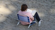 Stock Video Footage of heavyset woman reading on beach
