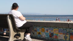 Heavyset woman on boardwalk bench Stock Footage