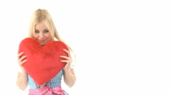 Woman cuddling with heart pillow - stock footage
