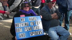 A woman holds a sign proclaiming her fear of spiders. - stock footage