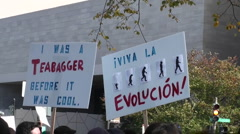 Stock Video Footage of Protestors hold signs at a rally which include the mention of tea baggers