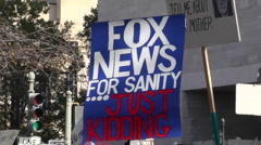 Stock Video Footage of A sign at a rally says Fox News For Sanity Just Kidding.