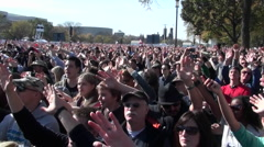 Stock Video Footage of People wave their arms at a giant outdoor gathering.