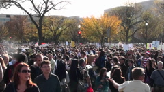 Huge crowds mill about at a political protest in Washington D.C. - stock footage