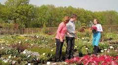 Female worker showing mature couple plant in garden centre Stock Footage