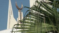 Islamic crescent behind fern tree in Islamabad, Pakistan Stock Footage