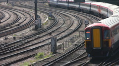 Electric express train rounds a curve to enter Victoria station London Stock Footage