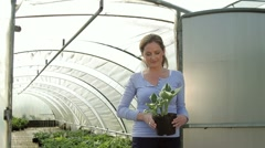 Portrait of female holding plant in front of green house Stock Footage