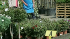 Mature male handing over plant to female in garden centre Stock Footage